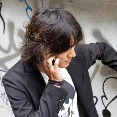 「壁に手をかけ電話する男性」の写真素材