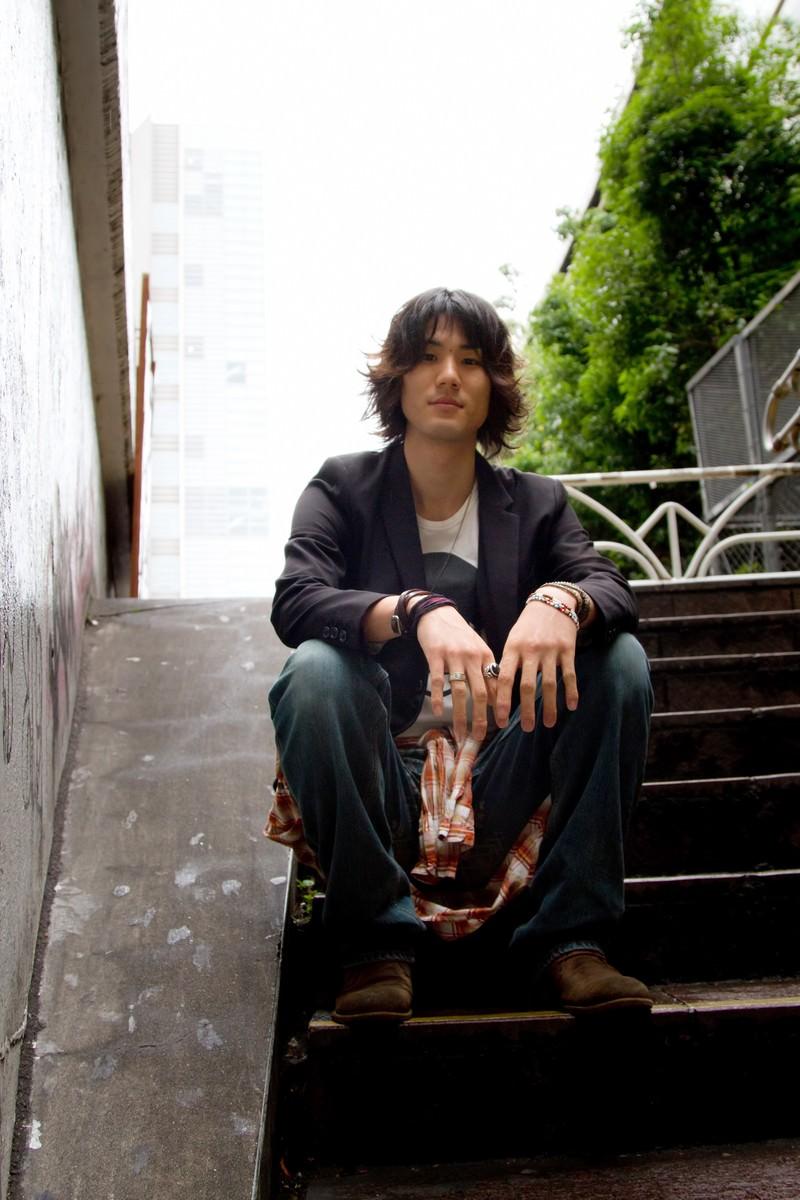 「階段に座り見下ろす男性」の写真[モデル:村田裕章]
