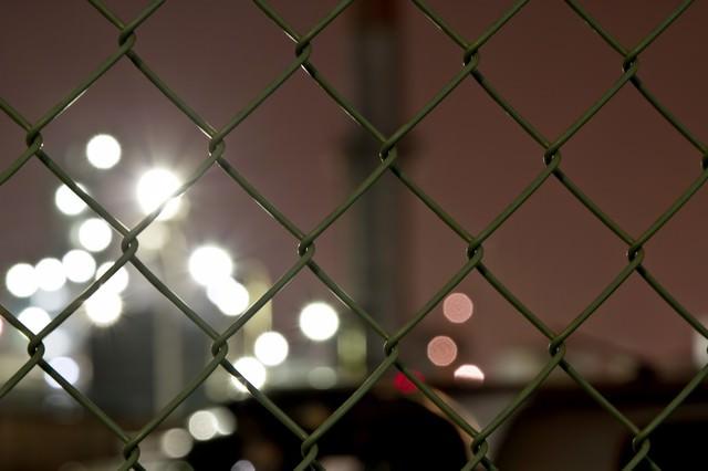 金網とボケる光の写真