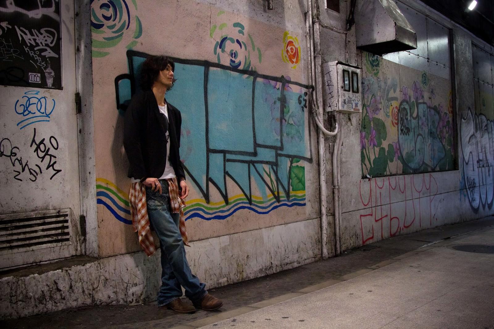 「渋谷の薄暗い高架下の落書きによりかかる若者」の写真[モデル:村田裕章]