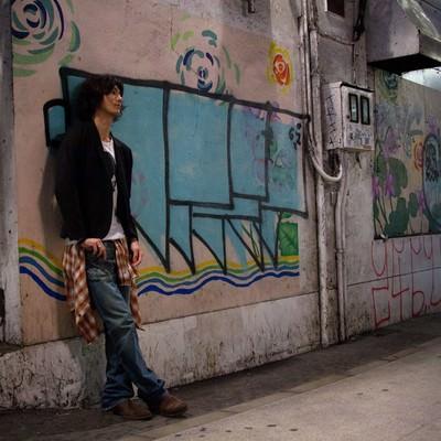 「渋谷の薄暗い高架下の落書きによりかかる若者」の写真素材
