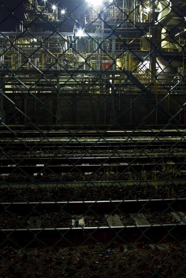 線路と夜の工場の写真