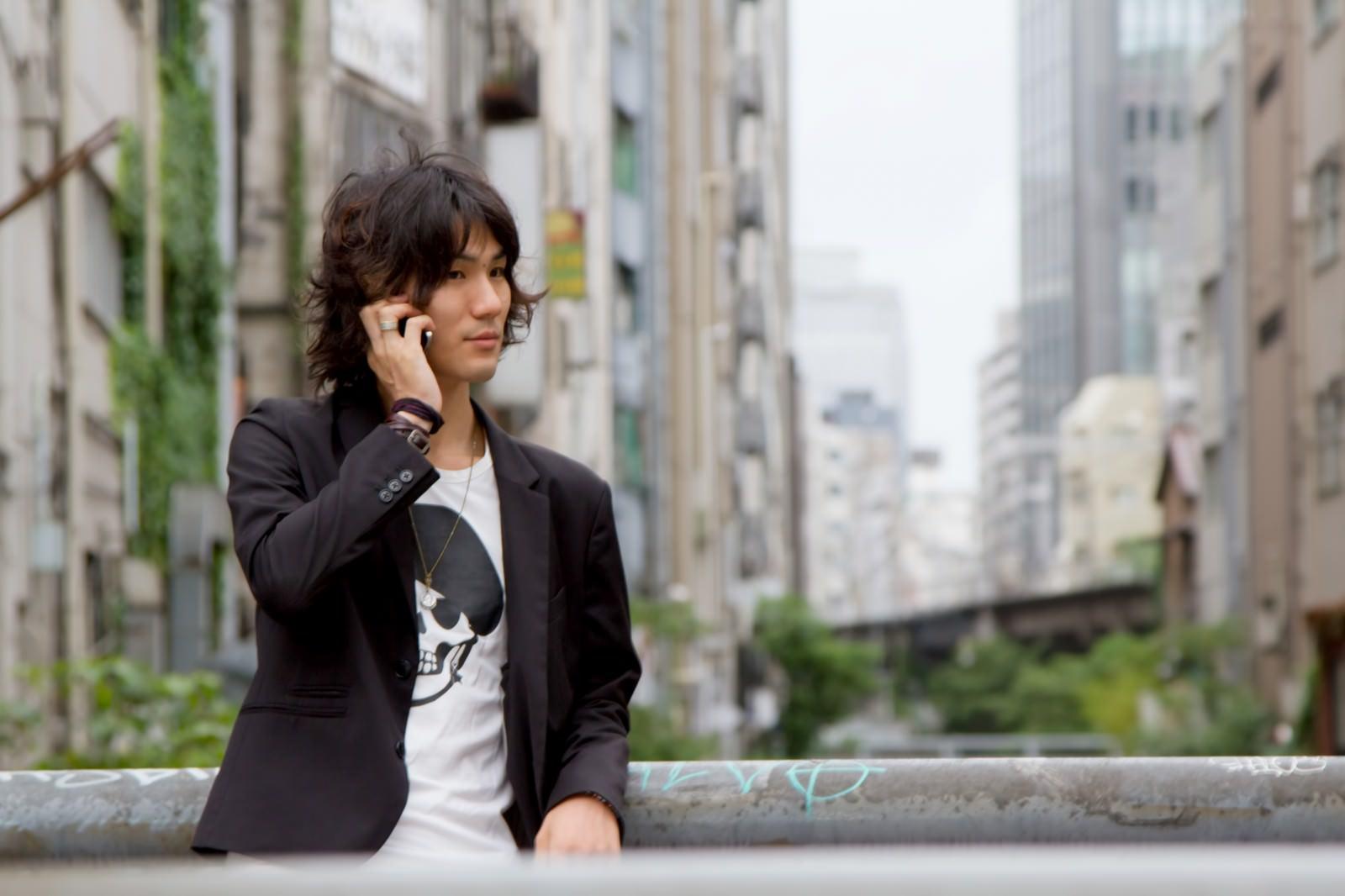 「渋谷川、橋の上で電話する男性」の写真[モデル:村田裕章]