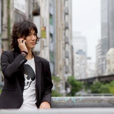 渋谷川、橋の上で電話する男性の写真