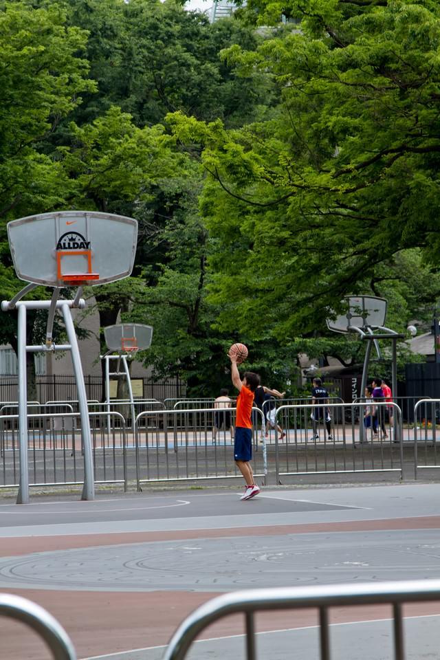 代々木公園のバスケットコートで練習する少年の写真