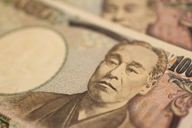 重ねた壱萬円札の写真