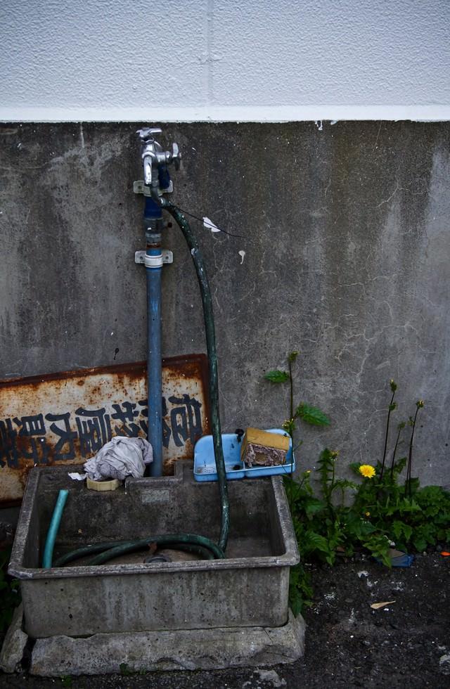 朽ちた水道と流し台の写真