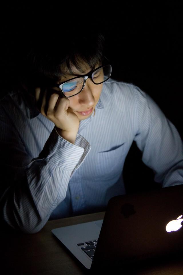 台風で帰宅できずに残業しうなだれる男性の写真