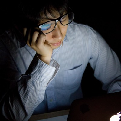 「台風で帰宅できずに残業しうなだれる男性」の写真素材