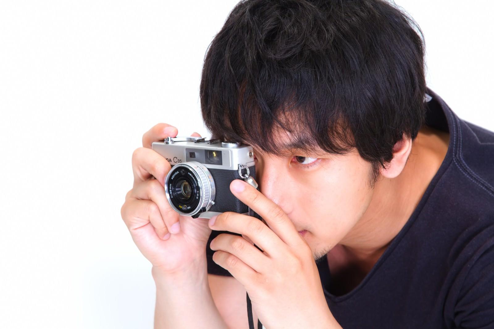 「「僕は撮り逃さない」とカメラを構える男性」の写真[モデル:大川竜弥]