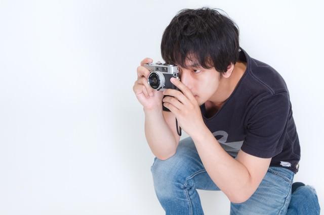 しゃがみこんでカメラを構える男性の写真