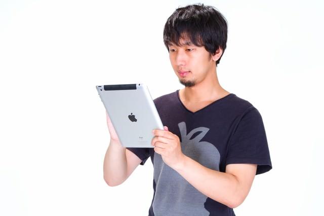 iPad をいじる男性の写真