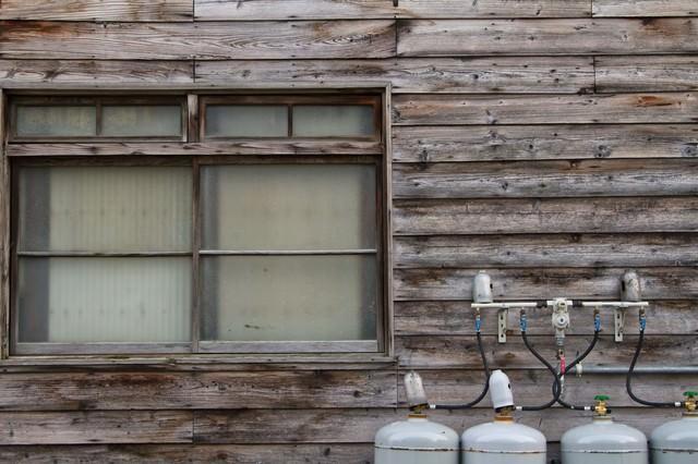 古い板張りの民家と窓の写真