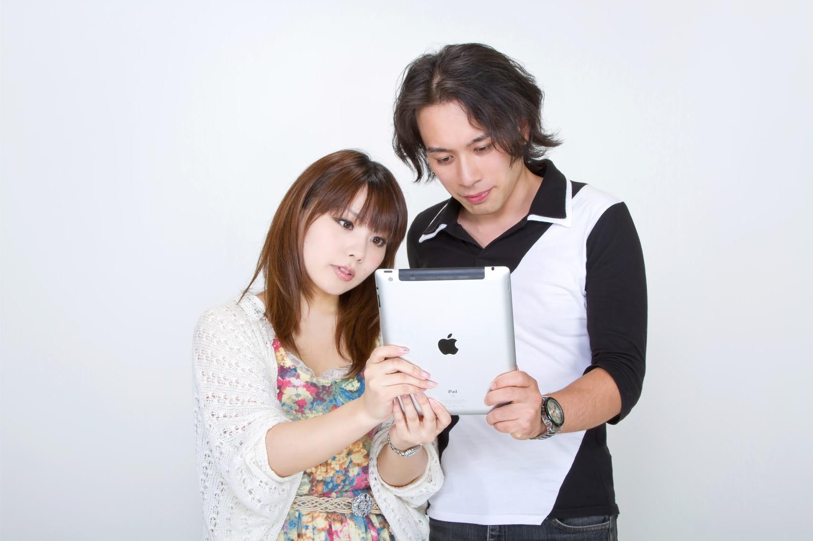「仲良くiPadを見る恋人」の写真[モデル:マイケルリュー Lala]