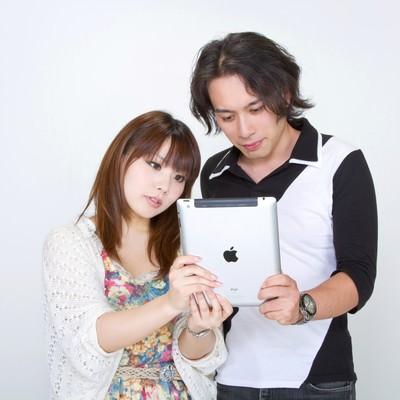 仲良くiPadを見る恋人の写真
