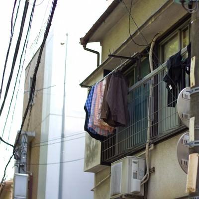 洗濯物が干された下町のアパートの写真