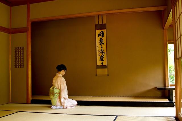 掛け軸の前で正座する着物女性の写真