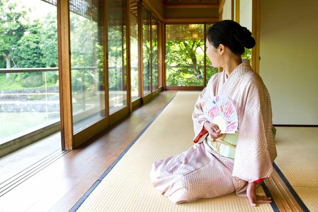 緑が見える廊下で扇子を持ち座る着物の女性の写真