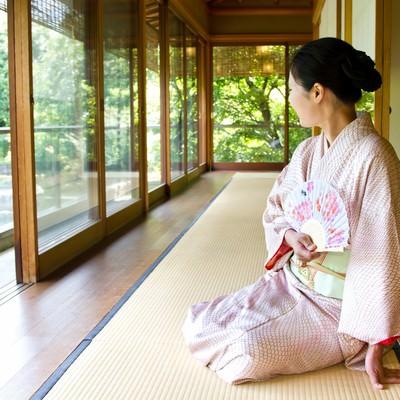 「緑が見える廊下で扇子を持ち座る着物の女性」の写真素材