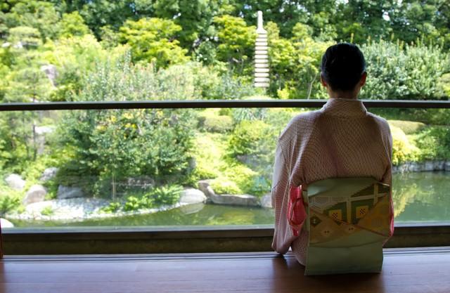 縁側で庭園を見る着物の女性の写真