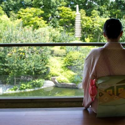 「縁側で庭園を見る着物の女性」の写真素材
