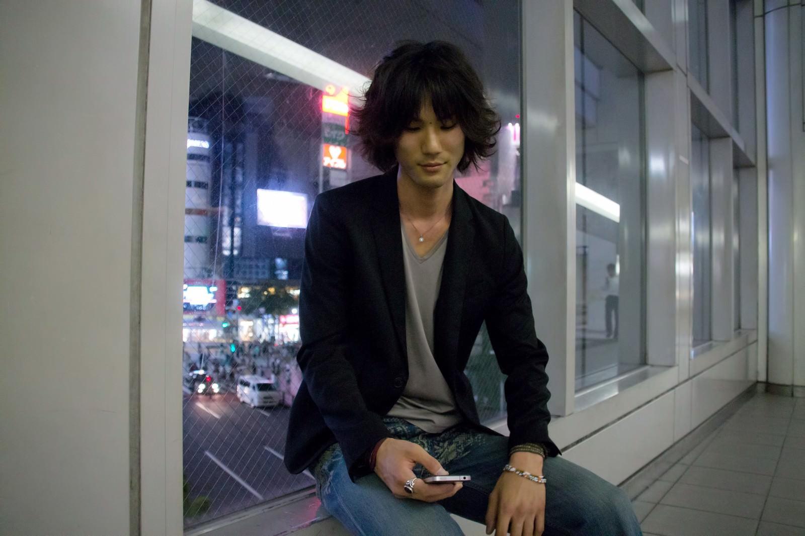 「座ってスマホをいじる若者座ってスマホをいじる若者」[モデル:村田裕章]のフリー写真素材を拡大