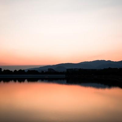 夕暮れと反射する水面の写真