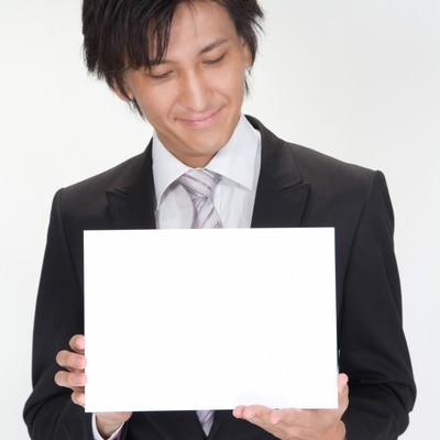 「白いボードを見るビジネスマン」の写真素材