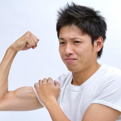 「力こぶを見せる男性」の写真素材