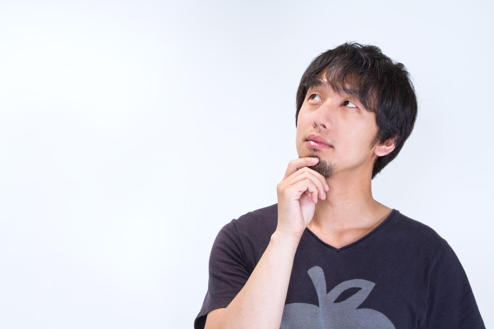 「ヒゲをいじり上を見上げる男性」の写真[モデル:大川竜弥]