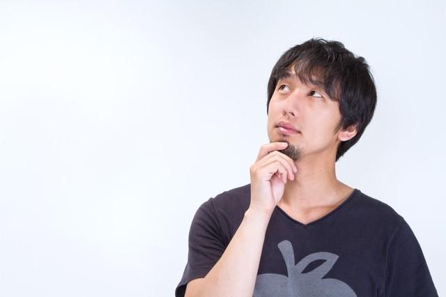 ヒゲをいじり上を見上げる男性の写真