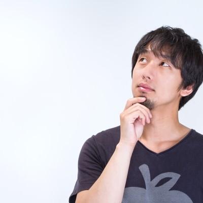 「ヒゲをいじり上を見上げる男性」の写真素材