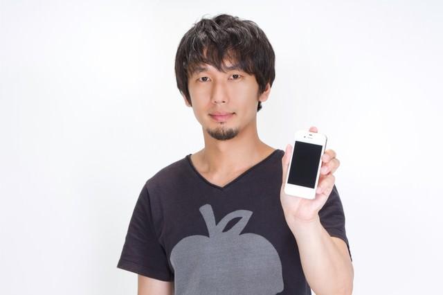スマートフォンの画面を見せる男性の写真
