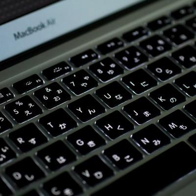 暗がりで光るMBA(キーボード)の写真
