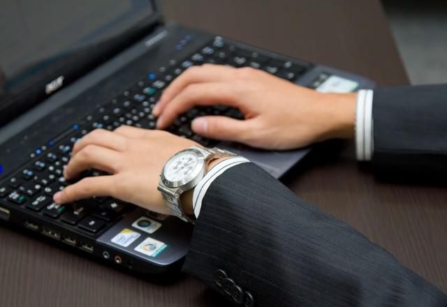 ノートPCを触るビジネスマンの写真