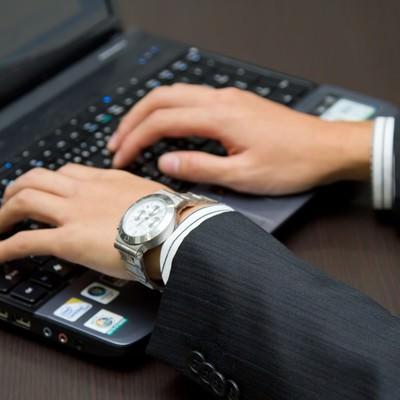「ノートPCを触るビジネスマン」の写真素材