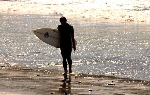 砂浜を歩くサーファーの写真