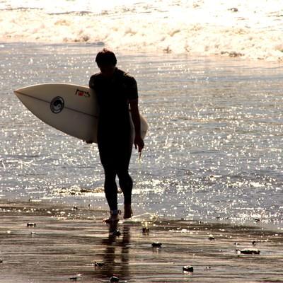 「砂浜を歩くサーファー」の写真素材