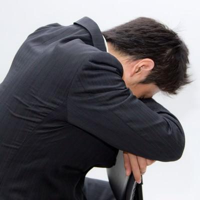 「椅子の背もたれにうなだれるビジネスマン」の写真素材