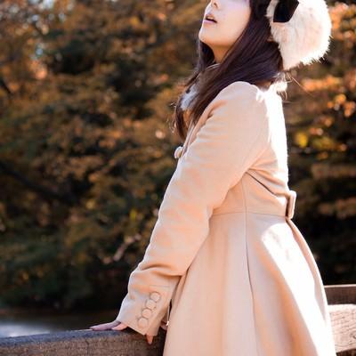 紅葉を見上げるコートの女性の写真