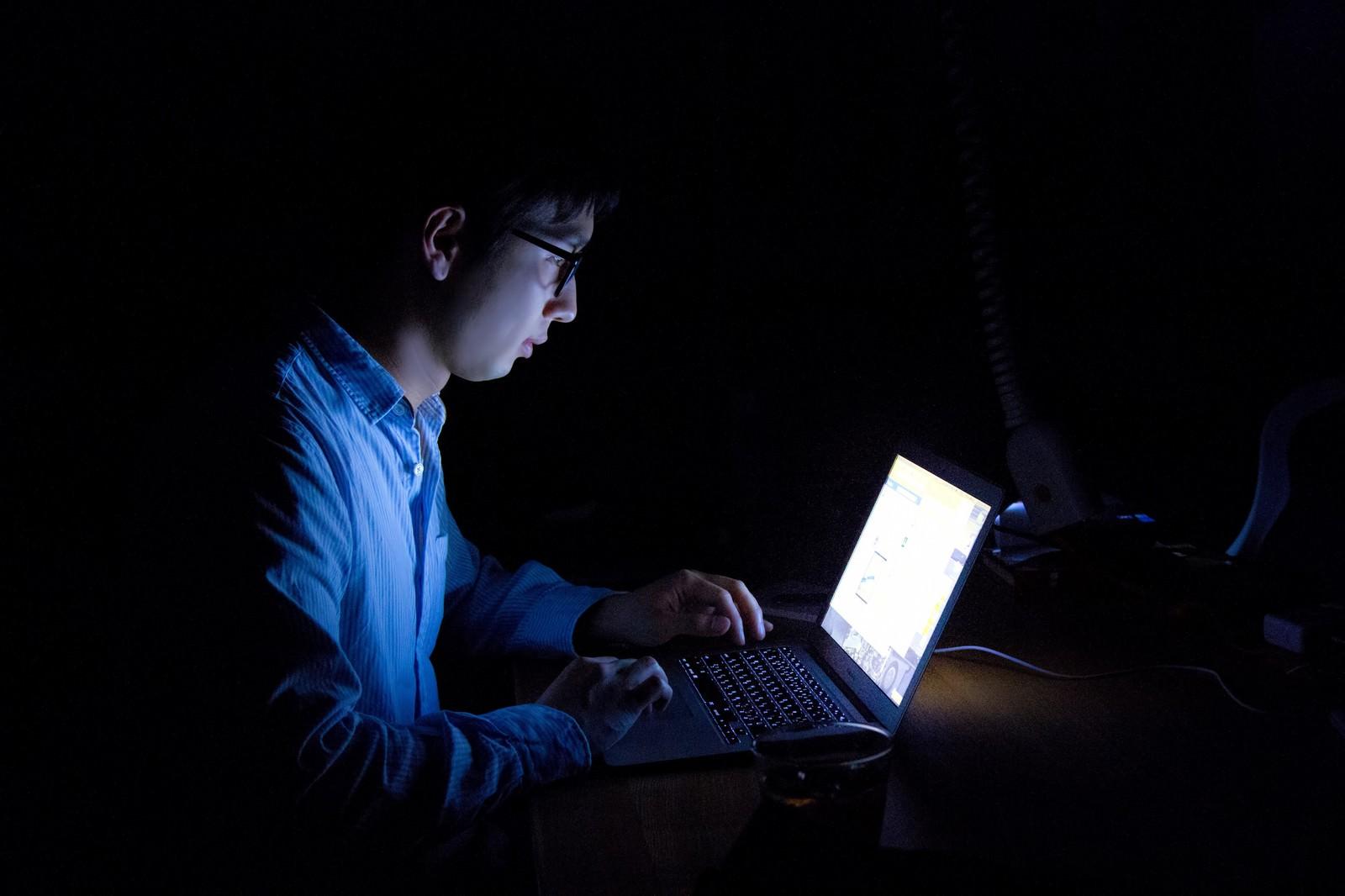 「暗闇でPCを使う残業中の男性 | 写真の無料素材・フリー素材 - ぱくたそ」の写真[モデル:大川竜弥]