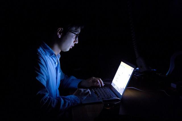 暗闇でPCを使う残業中の男性の写真