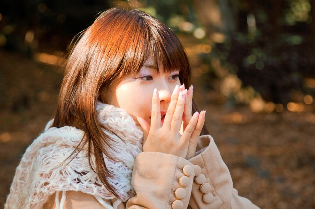 手を温めるマフラーの女の子の写真
