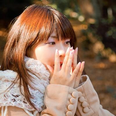 「手を温めるマフラーの女の子」の写真素材