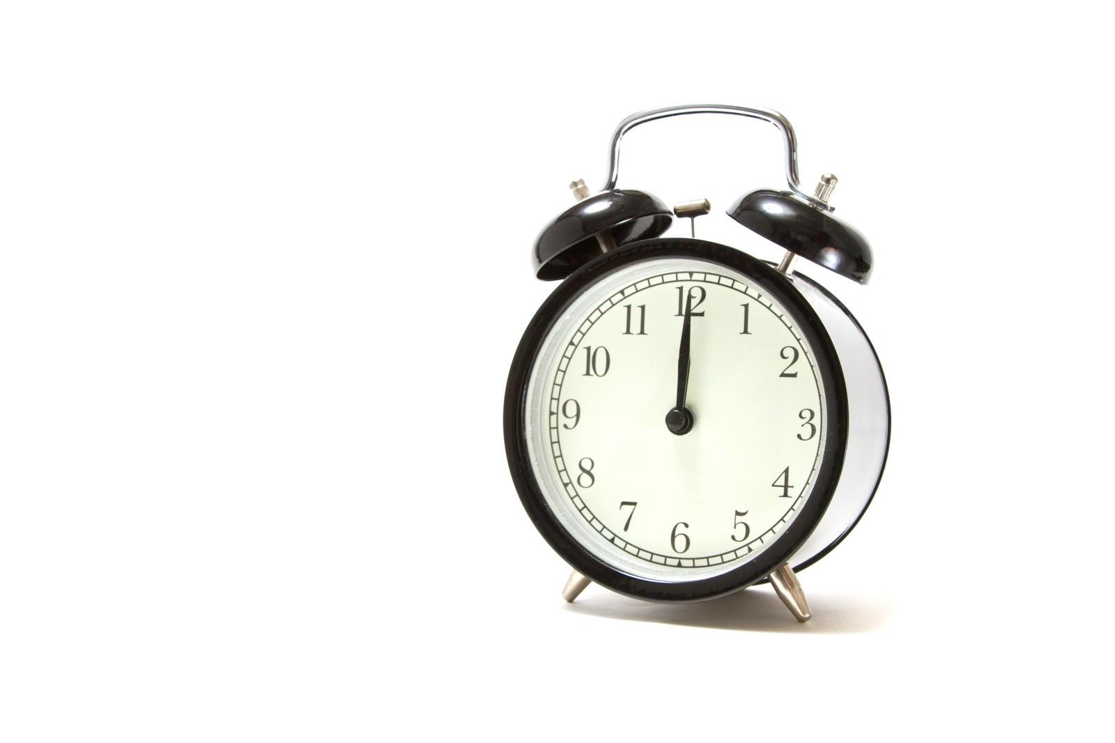 「お昼の時間を指す目覚まし時計」の写真