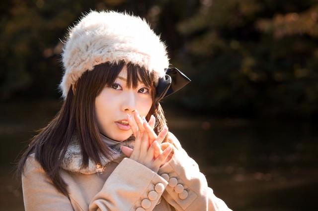 寒くて息で手を温めるロシア帽の女性の写真