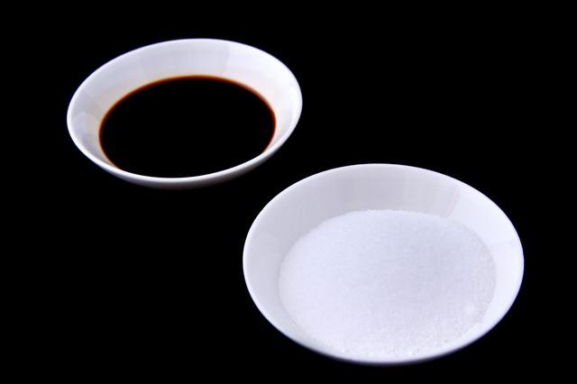 お皿に乗った塩と醤油の写真