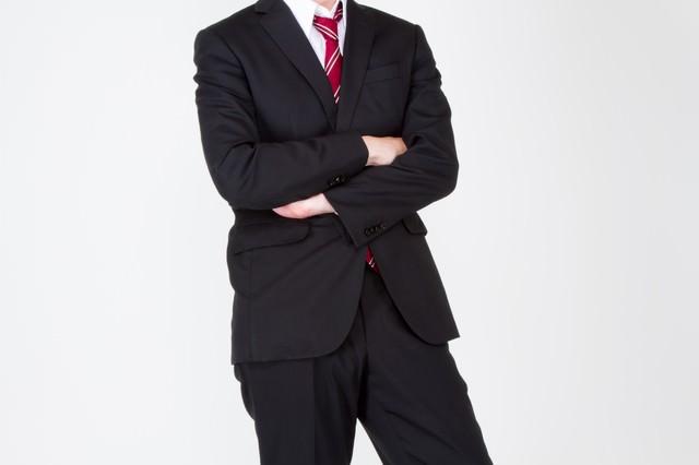 腕を組むスーツ姿の男性の写真