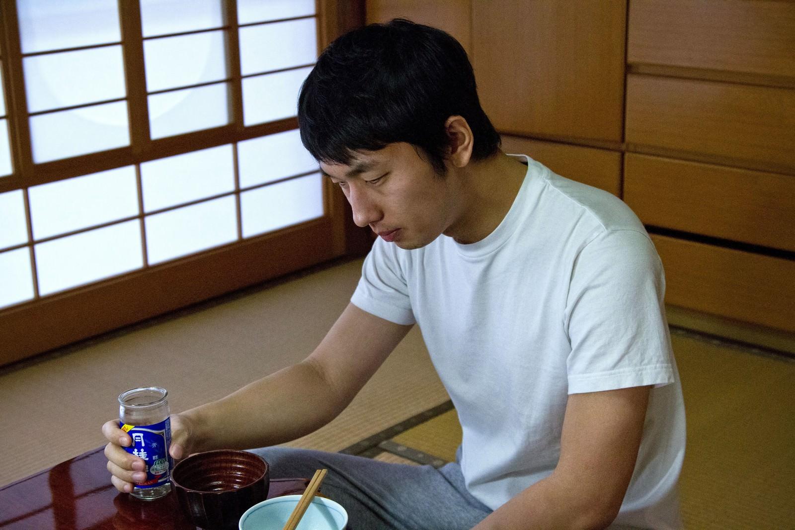 「お酒を持ちながら食卓でうなだれる男性」の写真[モデル:大川竜弥]