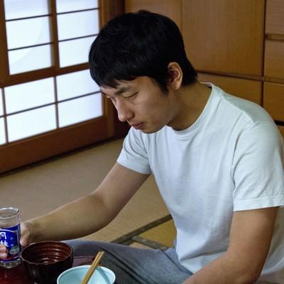 お酒を持ちながら食卓でうなだれる男性の写真